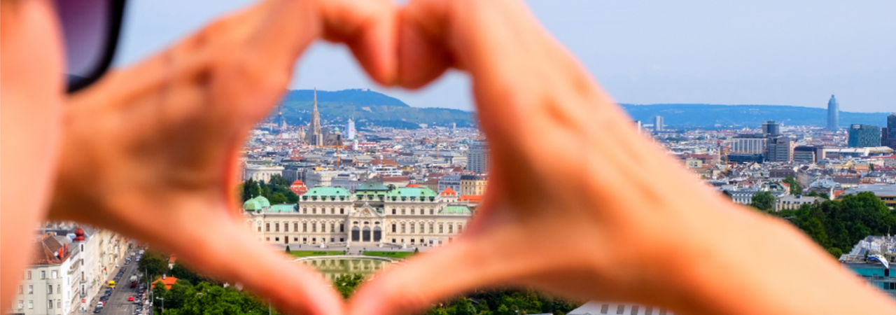 Two hands are forming a heart, through which one can see the panorama of the city of Vienna